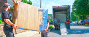 movers carrying a large item wrapped in brown paper