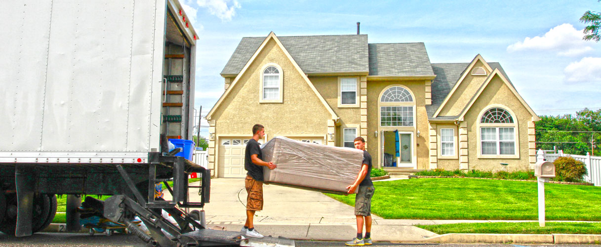Movers unload a sofa into a new home.