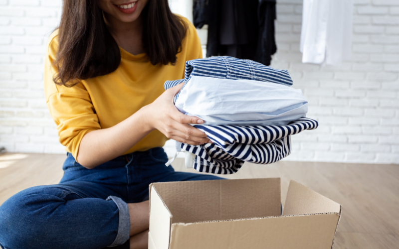 Woman packing linen shirts in cardboard box
