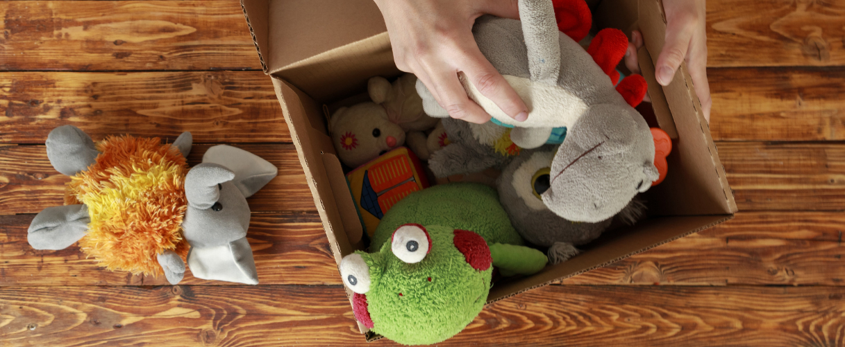 Person packing stuffed toys in a cardboard box
