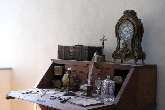 an antique desk with an antique clock