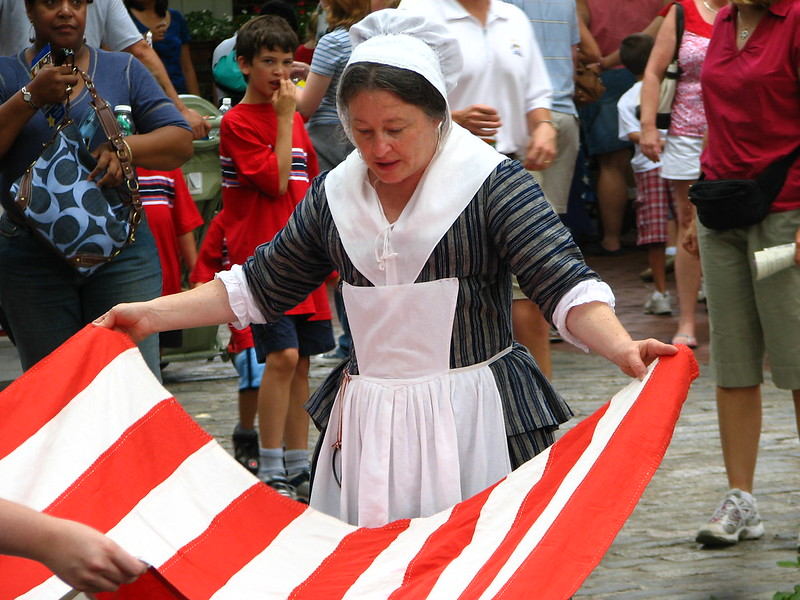 Woman in 18th century clothing and bonnet holding a flag