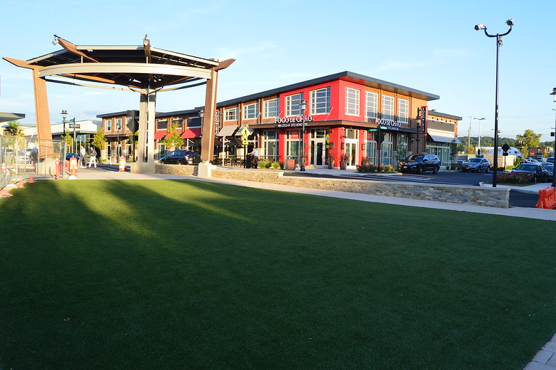 a shopping plaza with a green lawn and gazebo