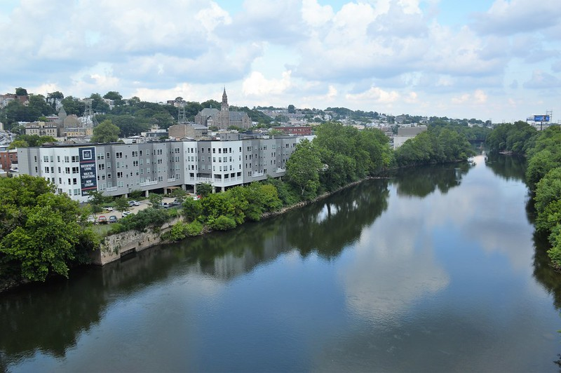 a river with a white building and city skyline beyond