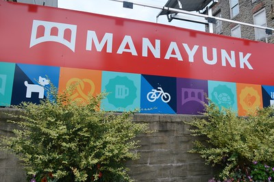 "A sign that says ""Manayunk"" and has icons for a pretzel, beer, bike and bridge"